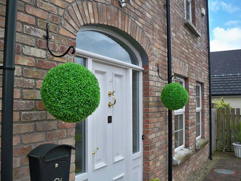 Topiary balls at entrance to house
